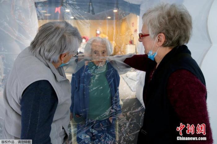 """当地时间12月4日,法国热蒙一家养老院内,Marie-Paule和Marie-Josephe隔着塑料帘探望97岁的母亲。这家养老院设置塑料""""探亲帘"""",方便疫情期间老人与家人的团聚。"""