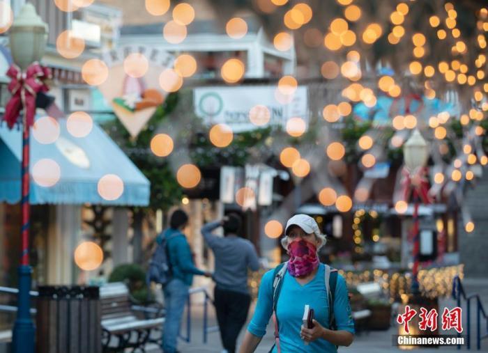 当地时间12月7日,美国加州旧金山市民佩戴口罩出行。《旧金山纪事报》报道称,截至12月5日的一个星期中,加州的新冠病毒检测阳性率跃升至9.7%。这意味着每10位接受病毒检测的加州人当中,就有1人的检测结果呈阳性。 记者 刘关关 摄