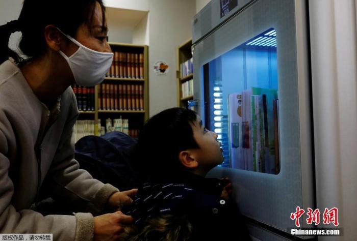 当地时间12月9日,䱳防止新冠肺炎疫情的进一步传播,日本东¶一所图书馆用紫外线给借出以及归还的图书做消毒处理。