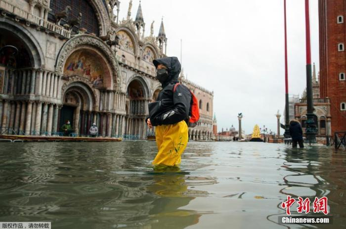 """当地时间12月8日,意大利威尼斯遭遇洪水侵袭,城内多地被淹。据悉,洪水是由强于预期的大风抬高水位引起,防止威尼斯被洪水侵袭的""""摩西系统""""未能发挥作用。图为行人在过膝的洪水中行走。"""
