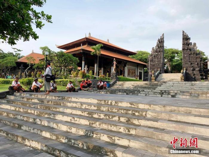 12月10日,距印度尼西亚发生新冠肺炎疫情已过去9个多月,巴厘岛作为国际著名旅游目的地,旅游业遭受重创。图为几名导游在巴厘岛海神庙景点前等候游客。 <a target='_blank'  data-cke-saved-href='http://www.chinanews.com/' href='http://www.chinanews.com/'>中新社</a>发 赖洪元 摄