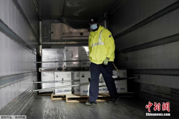工作人员将疫苗箱堆放在集装箱内。