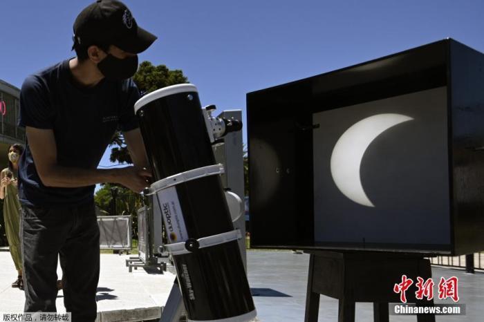 当地时间12月14日中午,今年唯一一次日全食在南美洲上演,阿根廷和智利部分地区可以观测到日全食,乌拉圭、巴西、巴拉圭、玻利维亚等国家也可观测到日偏食。图为男子将日全食投影到幕布上。
