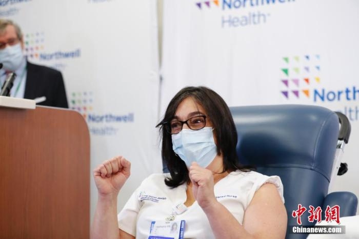 当地时间12月14日,纽约长岛犹太医疗中心护士史蒂芬妮接种新冠疫苗后作出胜利表情。当日,辉瑞vns85978威尼斯城官网首批近300万剂新冠疫苗陆续运抵美国各地。 中新社记者 廖攀 摄