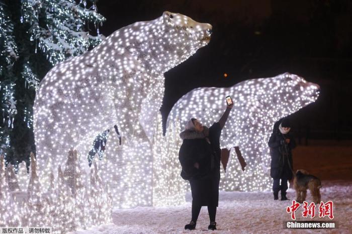 当地时间12月15日,俄罗斯莫斯科一公园内亮起北极熊彩灯雕塑,迎接即将到来的圣诞节和新年。图为民众被北极熊彩灯雕塑吸引玩起自拍。