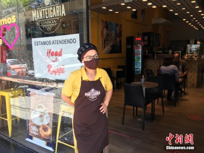 当地时间12月16日,巴西圣保罗,一名女服务员戴着口罩在一家餐馆门口迎客。据巴西卫生部公布的数据,截至16日18时,巴西累计新冠肺炎确诊病例超704万例,累计死亡超18.3万例。其中,疫情最严重的圣保罗州累计确诊病例逾134.1万例、死亡逾4.4万例。 中新社记者 莫成雄 摄