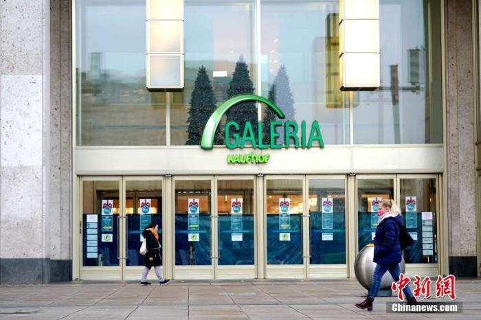 """资料图:当德国全国实施被称为""""硬性封城""""的严格防疫措施,大部分商铺以及中小学、幼儿园均被关闭,私人聚会不得超过5人,一些州还颁布了宵禁令。图为当天下午,路人经过柏林亚历山大广场一家已停业的德国最大连锁百货公司考夫霍夫百货门店。 中新社记者 彭大伟 摄"""