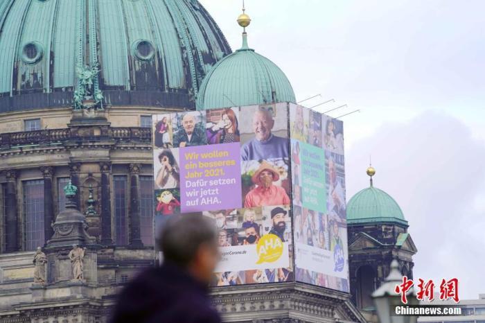 图为路人经过柏林大教堂上的巨幅防疫广告。 记者 彭大伟 摄