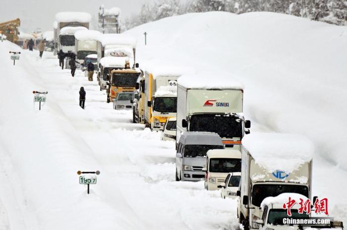 当地时间2020年12月18日,日本新��市南鱼沼市遭遇暴雪,大量车辆被堵在路上,扫雪工作已同步展开。 图片来源:视觉中国