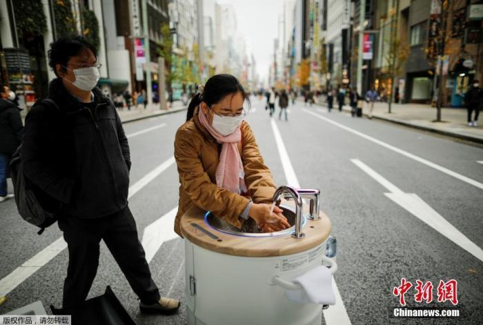 """当地时间12月19日,日本东京银座购物区,一位女士使用名为""""WOSH""""的移动式洗手机进行洗手清洁。这台机器可以为路人提供方便的洗手清洁服务,有助防范新冠病毒。"""