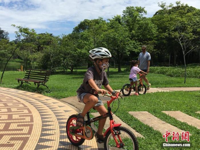 当地时间12月21日,巴西圣保罗,一名儿童戴着口罩在当地一公园骑车锻炼。据巴西卫生部公布的数据,截至21日18时,巴西新冠肺炎确诊病例累计超726万例,累计死亡超18.7万例。其中,圣保罗州累计确诊病例逾138.8万例、死亡逾4.5万例。 <a target='_blank' href='http://www.chinanews.com/'>中新社</a>记者 莫成雄 摄