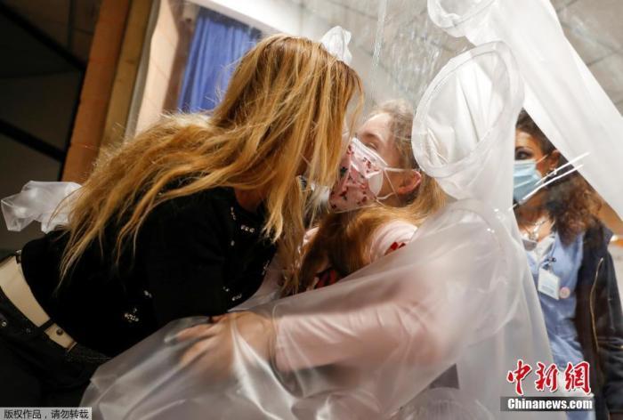 """资料图:当地时间12月22日,意大利罗马圣拉斐尔医院IRCCS的小儿康复和发育障碍部门设置""""拥抱屋"""",住院的孩童可以通过塑料薄膜与家人拥抱团聚。图为一名女孩和母亲相拥。"""