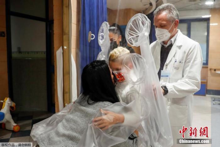 """当地时间2020年12月22日,意大利罗马圣拉斐尔医院IRCCS的小儿康复和发育障碍部门设置""""拥抱屋"""",住院的孩童可以通过塑料薄膜与家人拥抱团聚。"""