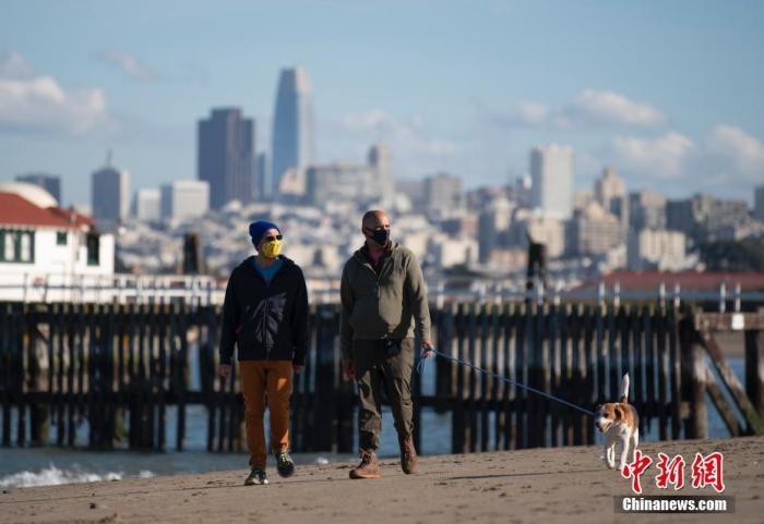 当地时间12月27日,美国加州旧金山市民在海边休闲。美国约翰斯·霍普金斯大学当日发布的新冠疫情最新统计数据显示,美国累计确诊病例超过1900万例。中新社记者 刘关关 摄