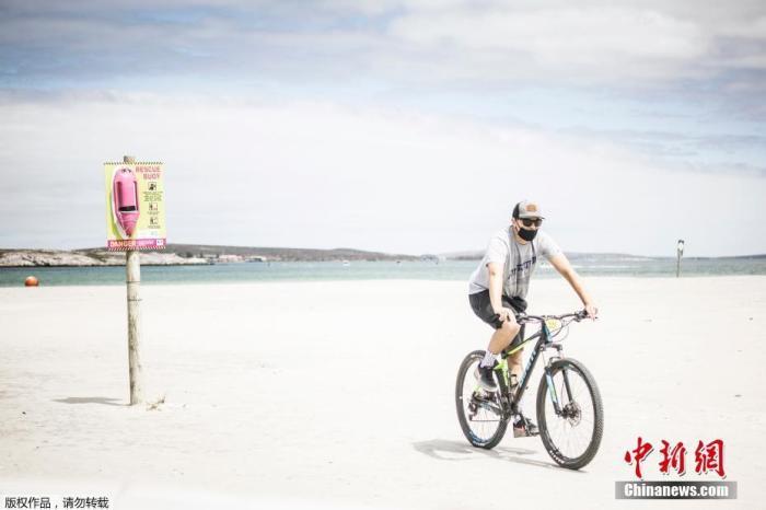 """当地时间2020年12月29日,南非兰格班,一名游客在海滩骑车。南非总统拉马福萨28日发表全国电视讲话时宣布:为应对当前第二轮新冠肺炎疫情高峰,南非政府决定将针对疫情的""""封锁令""""水平从一级升至三级。"""