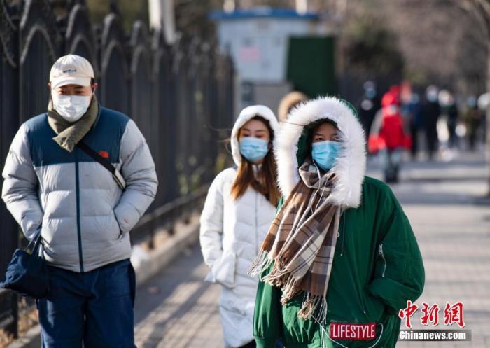 资料图:市民身着各式保暖装备出行。 记者 侯宇 摄