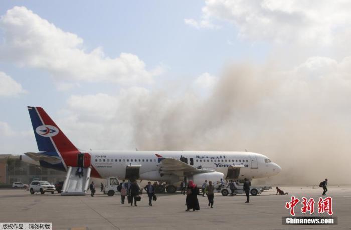 当地时间12月30日,一架载有也门联合政府成员的飞机抵达亚丁机场后不久,机场发生爆炸事件,现场烟尘滚滚。一名安全部门消息人士透露,爆炸事件导致多人受伤,其中没有政府官员。图为停机坪上一架航班的乘客通过紧急通道逃生。