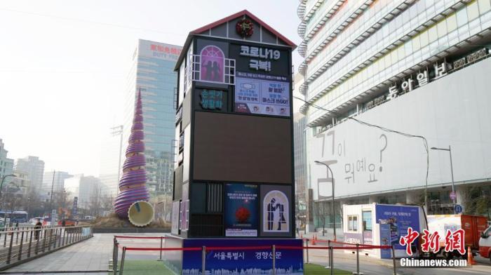 """12月底,首尔市中心清溪广场上建起一个灯箱,其上投影出几个短句――""""一起战胜""""""""共克疫情""""。 中新社记者 曾鼐 摄"""