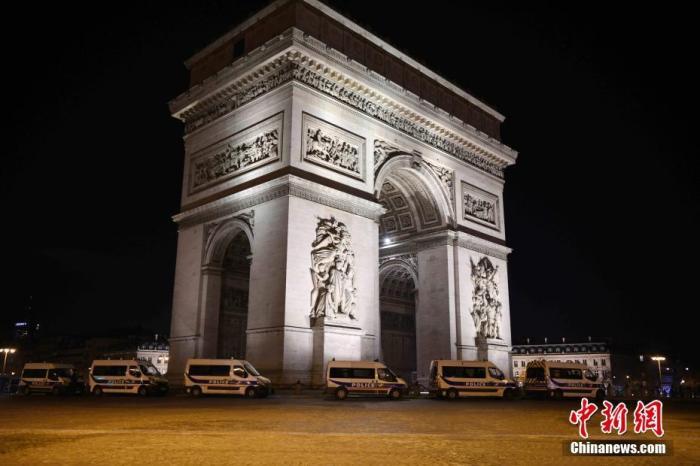 当地时间2020年12月31日晚,法国在跨年夜严格实施宵禁,以应对新冠肺炎疫情。大批警力部署在巴黎市中心,监督民众遵守宵禁令。图为多辆警车当晚部署在凯旋门周围。<em></em> 中新社记者 李洋 摄