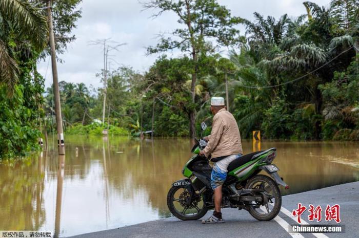 2021年1月4日,马来西亚彭亨州兰昌附近,一名骑摩托车的男子被洪水拦住去路。