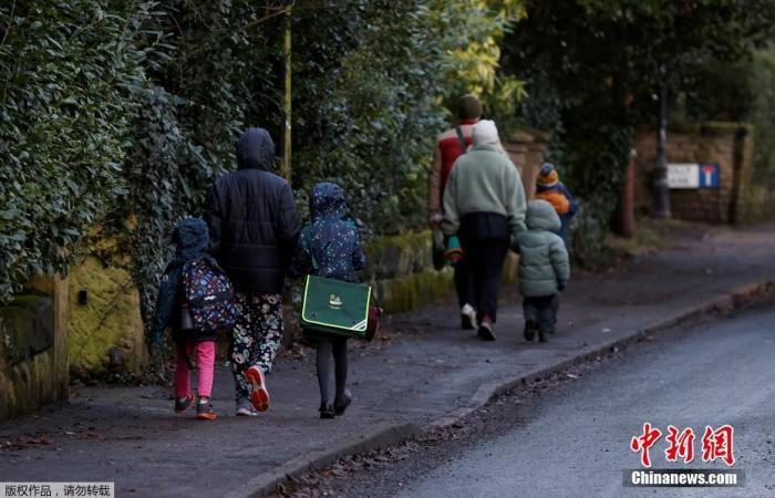 1月5日消息,英国疫情严峻,学生上学依旧。新冠肺炎爆发期间,学生们在新学期的第一天步行上学。