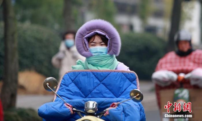 """2021年1月5日,是小寒节气,受强冷空气影响,江苏省扬州市气温骤降,最低气温降至零下3摄氏度,市民纷纷""""全副武装""""抵御寒冷。 图片来源:视觉中国"""