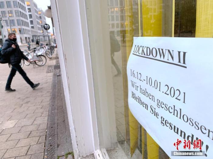 """1月5日,德国累计确诊感染新冠病毒人数超过180万。德国总理默克尔当天在与各州州长商议后宣布,将目前实施的全国性""""封城""""措施延长至1月31日,同时进一步加强""""封城""""力度,包括每个家庭最多只能与一个外人聚会、疫情热点地区居民活动半径不能超出住所周边15公里。图为当天,行人经过柏林一家已经关闭的花店。该店橱窗上张贴有""""由于第二轮封城关闭""""的告示。 中新社记者 彭大伟 摄"""