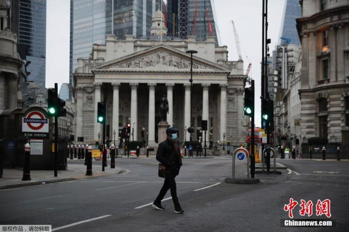 當地時間1月5日,英國采取了第三次嚴格性封鎖措施,倫敦街頭行人稀少。圖為一名行人穿過英國皇家交易所前的街道。