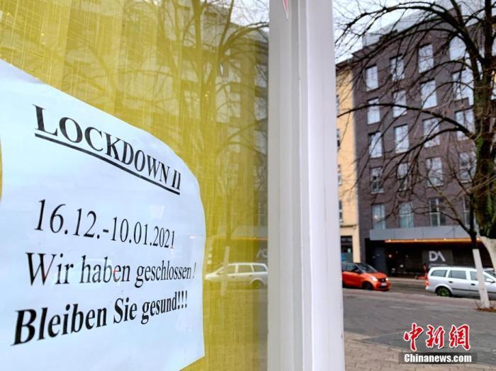 """1月5日,德国累计确诊感染新冠病毒人数超过180万。德国总理默克尔当天在与各州州长商议后宣布,将目前实施的全国性""""封城""""措施延长至1月31日,同时进一步加强""""封城""""力度,包括每个家庭最多只能与一个外人聚会、疫情热点地区居民活动半径不能超出住所周边15公里。图为当天,柏林一家已经关闭的花店在橱窗上张贴的""""由于第二轮封城关闭""""的告示。 中新社记者 彭大伟 摄"""