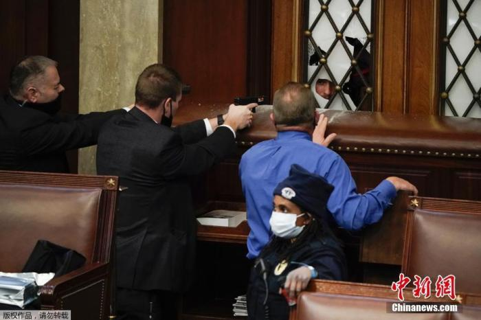 当地时间1月6日,美国参众两院确认选举人团投票结果的联席会议,因现任总统特朗普支持者闯入国会大厦引发大规模骚乱而被迫中断,现场极度混乱。图为警察在美国国会众议院内举枪与特朗普支持者对峙。