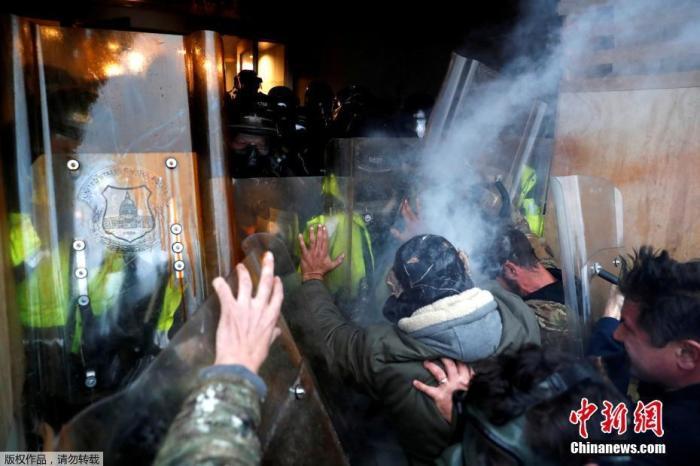 当地时间1月6日,美国参众两院确认选举人团投票结果的联席会议,因现任总统特朗普支持者闯入国会大厦引发大规模骚乱而被迫中断,现场极度混乱。图为特朗普支持者与国会大厦警察发生冲突。