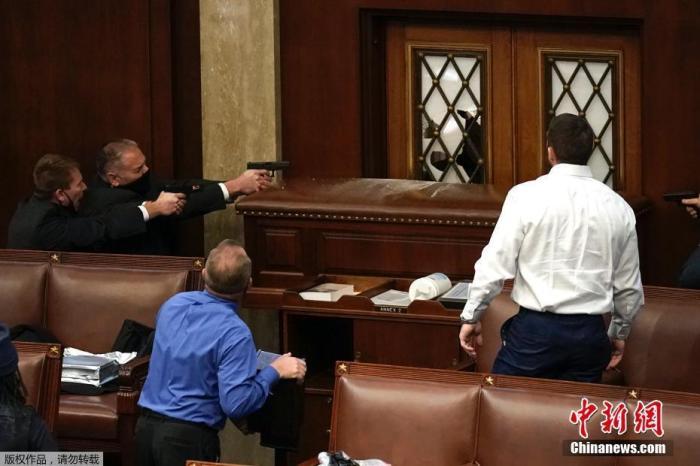 资料图:当地时间1月6日,美国国会参众两院召开联席会议期间,特朗普支持者闯入国会大厦引发骚乱,在众议院内警察隔着门窗持枪与抗议者对峙。