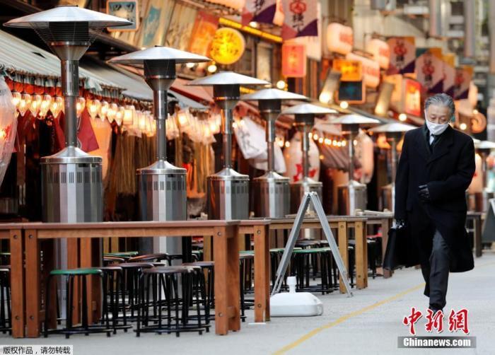 质料图:当地时间1月7日,日本东京,一名路人路过空荡的户西餐馆。