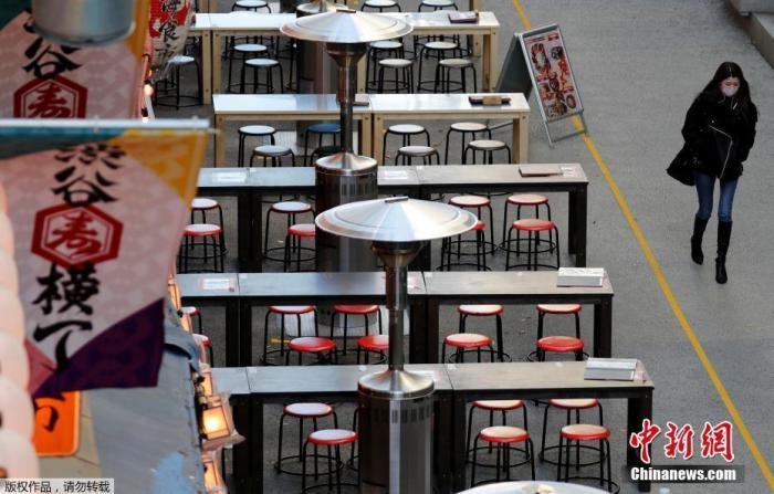 资料图:当地时间1月7日,日本东京,一名路人路过空荡的户外餐馆。
