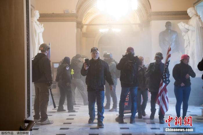当地时间1月6日,美国参众两院确认选举人团投票结果的联席会议,因现任总统特朗普支持者闯入国会大厦引发大规模骚乱而被迫中断,现场极度混乱。图为特朗普支持者在国会大厦内抗议。