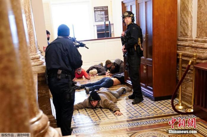 當地時間1月6日,美國參眾兩院確認選舉人團投票結果的聯席會議,因現任總統特朗普支持者闖入國會大廈引發大規模騷亂而被迫中斷,現場極度混亂。圖為被制服的特朗普支持者。