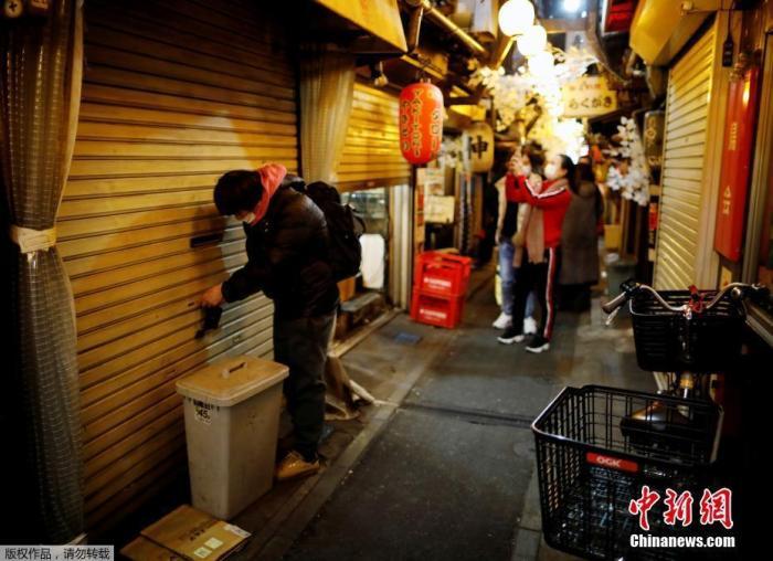 资料图:当地时间2021年1月8日,日本东京,一位工作人员锁上了店门。