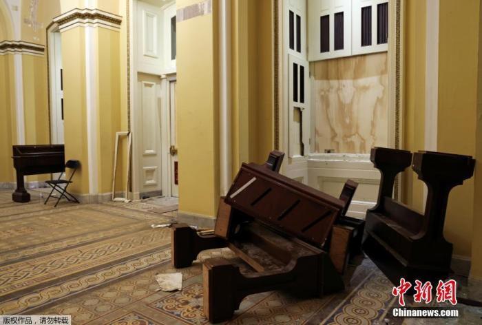 当地时间1月7日,美国华盛顿,特朗普声援者冲入国会大厦引发骚乱后,国会大厦内大量设施被损毁,现场一片狼藉。图为家具散落在走廊。