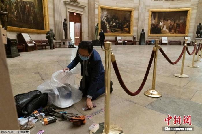 当地时间1月7日,美国华盛顿,特朗普支持者冲入国会大厦引发骚乱后,国会大厦内大量设施被损毁,现场一片狼藉。图为工作人员清理遗留的垃圾。