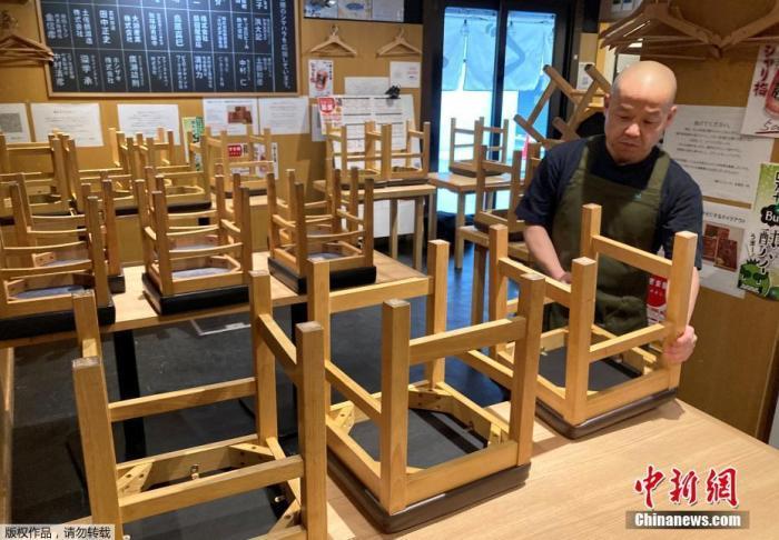 当地时间2021年1月8日,日本东京,一位餐厅老板正在收拾店内的座椅,准备关店。此前,因新冠疫情持续蔓延,日本首相菅义伟宣布,该国首都圈的一都三县(东京都、埼玉县、千叶县和神奈川县)从当地时间1月8日0时起进入紧急状态,结束时间为2月7日。据报道,紧急状态生效后,当局将强化防疫措施,包括要求相关地区的餐饮店缩短营业时间和对大型活动的举办进行限制等。