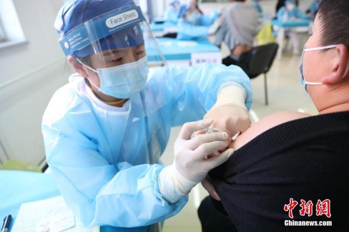 资料图:北京市海淀区学院路街道临时接种点内,医护人员为接种者注射疫苗。 中新社记者 蒋启明 摄
