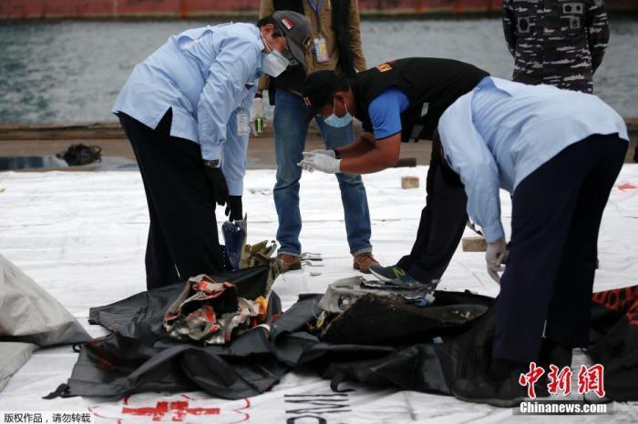 当地时间1月10日,印尼雅加达Tanjung Priok港,工作人员检查坠毁客机残骸。