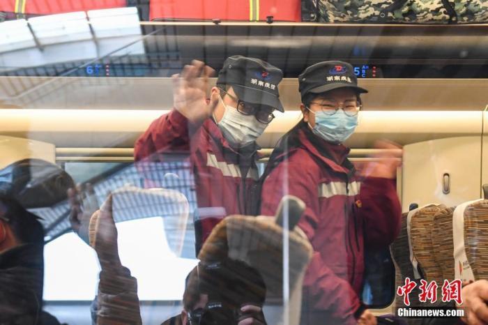 1月10日,湖南长沙,流调队员在车厢内向送行的人挥手道别。当日,湖南省流行病学调查队23名队员携带防护物资乘坐高铁前往河北省石家庄市,协助当地开展新冠肺炎疫情防控工作。 记者 杨华峰 摄