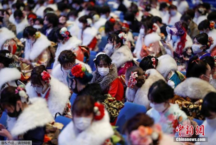 资料图:由于新冠疫情持续恶化,日本横滨,穿着和服戴着口罩的少女们参加成人礼。