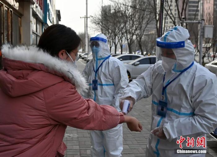 资料图:1月14日,河北石家庄市救助管理站工作人员为一名因疫情无法返乡的外地大学生测量体温。中新社记者 翟羽佳 摄