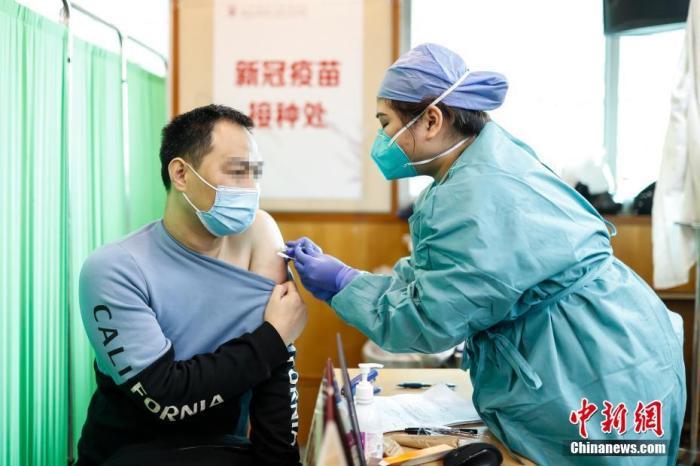 1月14日,医护人员在广东省广州市红十字会医院的接种点为出租车司机注射新冠疫苗。 中新社发 李佳能 摄