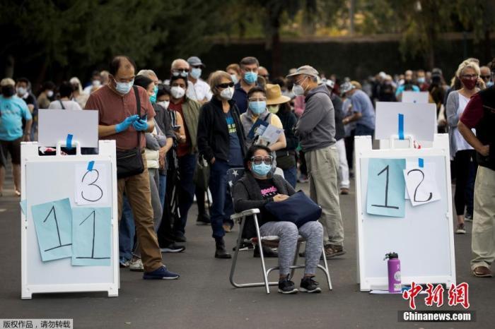 """当地时间2021年1月13日,美国加利福尼亚州安纳海姆,美国加利福尼亚州橙县政府宣布,政府在当地迪士尼乐园度假区内安置了大型临时新冠疫苗接种点,位于园区东南部。据路透社11日报道,迪士尼接种点建成后,将成为橙县首个大规模疫苗接种点。加州迪士尼乐园自2020年3月份以来一直处于关闭状态,园方医疗主管帕梅拉・海默尔称,""""能为抗疫工作做出贡献,我们非常荣幸""""。图为人们在加州迪士尼乐园度假区接种疫苗的地点排长队等候。"""