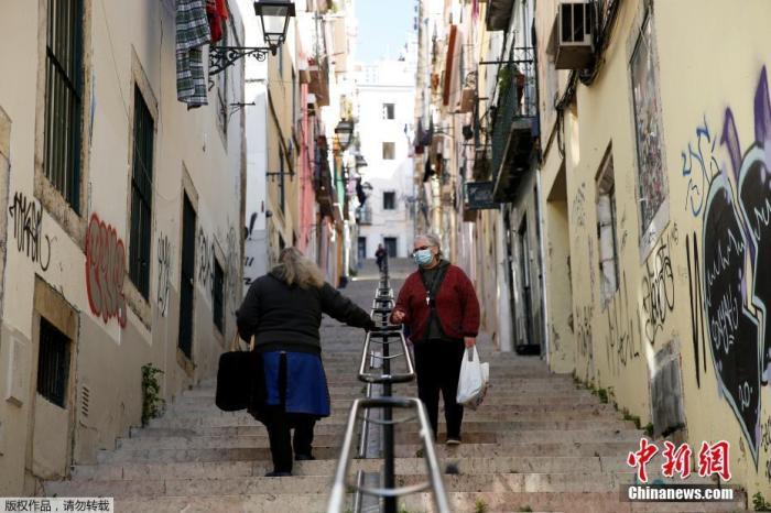 当地时间1月13日,葡萄牙里斯本两名带口罩的女子在楼梯上交谈。