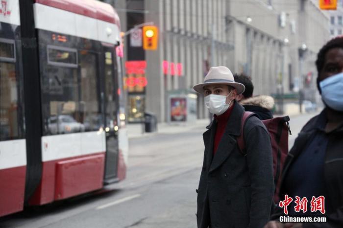 """当地时间1月14日,佩戴口罩的乘客在加拿大多伦多市中心等候公交车。多伦多所在的加拿大人口第一大省安大略省从当天开始实施""""居家令""""。该省已于12日宣布再次进入持续至少28天的省级紧急状态,以遏制严峻疫情。 中新社记者 余瑞冬 摄"""