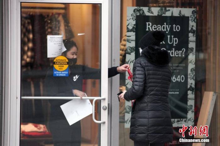 """当地时间1月14日,加拿大多伦多市中心一家暂时谢绝顾客入内的商户为顾客提供预约取货服务。多伦多所在的加拿大人口第一大省安大略省从当天开始实施""""居家令""""。该省已于12日宣布再次进入持续至少28天的省级紧急状态,以遏制严峻疫情。 中新社记者 余瑞冬 摄"""